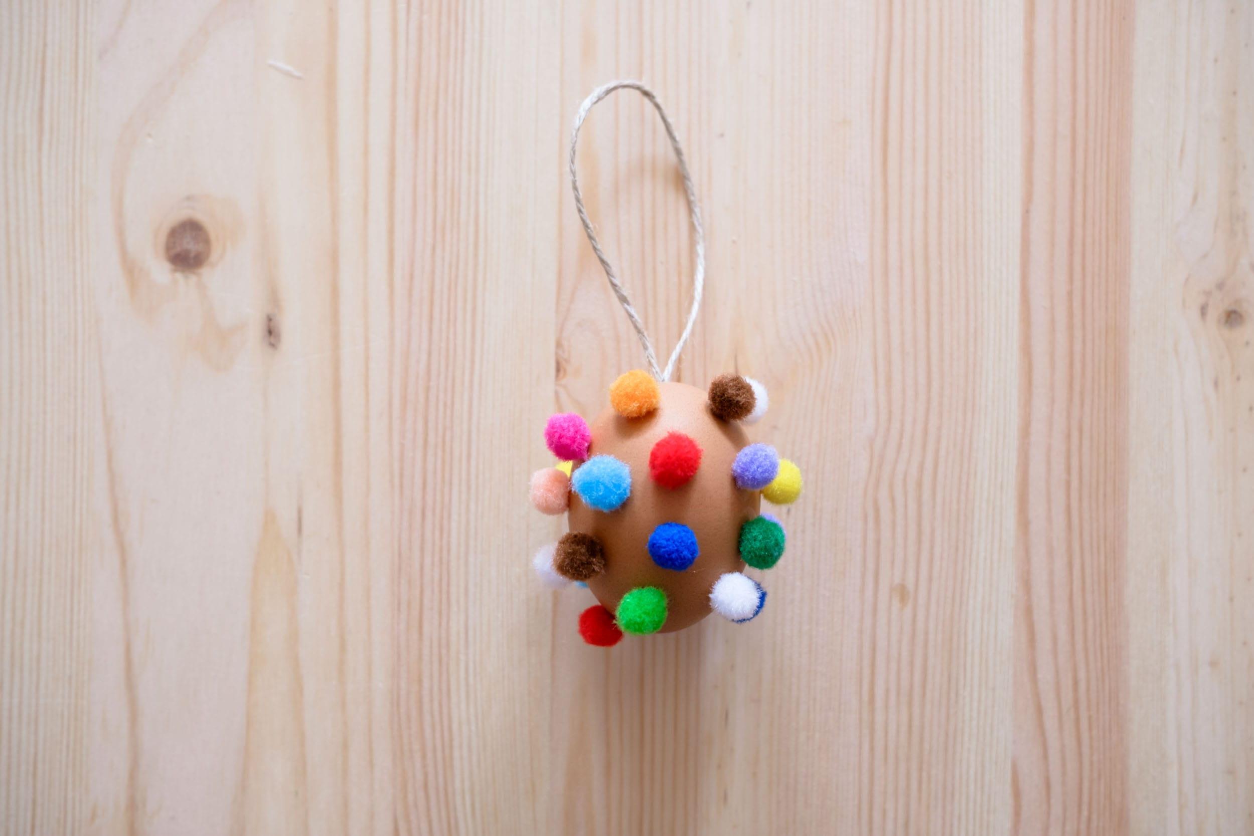 DIY Bunte Bommeleier | Osterdeko basteln | Ostereier mit bunten Bommeln | Anleitung | Basteln mit Kindern | Ostern | Osterzweig | #ostern #basteln #diy | Mehr auf https://ivy.li